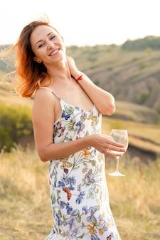 Mooi roodharig meisje heeft plezier en dansen in een veld bij zonsondergang.
