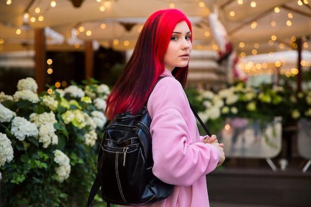 Mooi roodharig meisje in de avond op een verlichte stadsstraat.