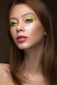 Mooi roodharig meisje met creatieve groene make-up