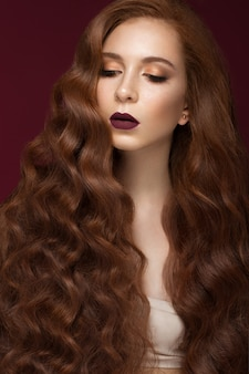 Mooi roodharig meisje met een perfect krullend haar en klassieke make-up. mooi gezicht.