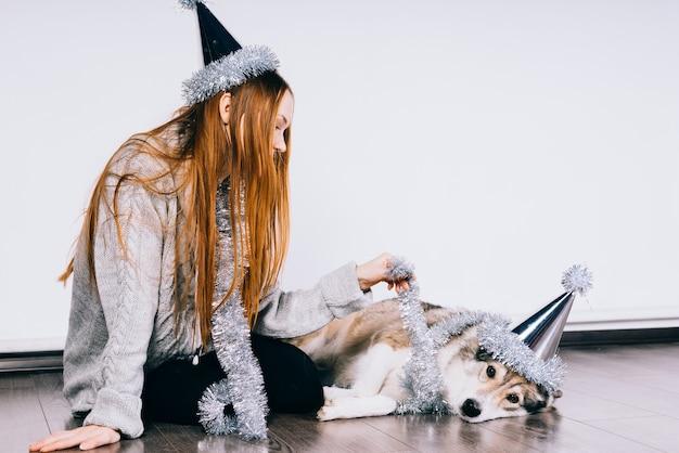 Mooi roodharig meisje met een pet op haar hoofd zit op de grond met haar grote hond, wachtend op een nieuw jaar en kerstmis