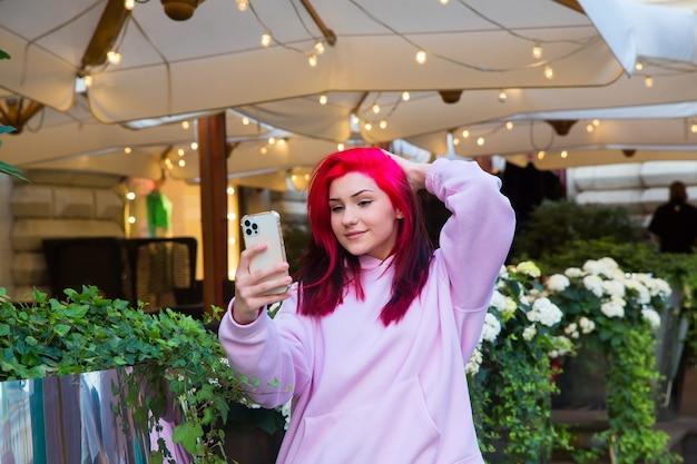 Mooi roodharig meisje neemt selfie op smartphone op straat in de stad.
