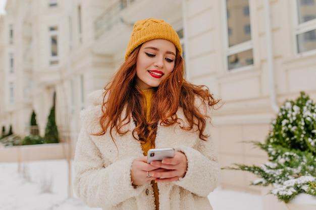 Mooi roodharig meisje sms-bericht. buiten foto van geïnteresseerde jonge vrouw in jas poseren met telefoon in de winter.