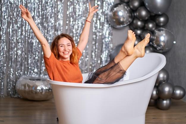 Mooi roodharig meisje verheugt zich zittend gekleed in bad