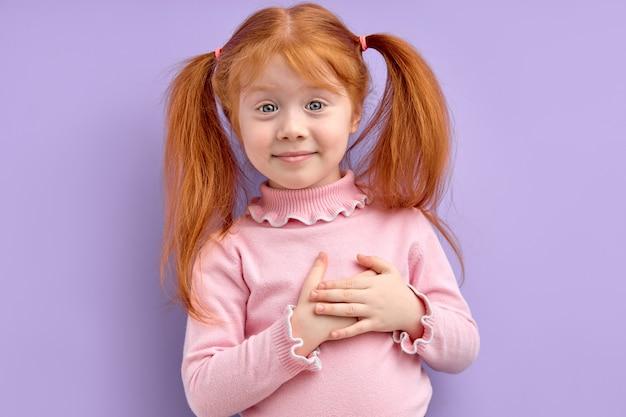 Mooi roodharige kind meisje hand in hand op de borst dankbaarheid voelen of dromen