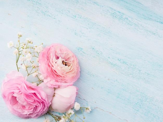 Mooi roze boterbloemenkader op houten turkoois. vrouw moederdag bruiloft. vakantie elegante bos bloemen.