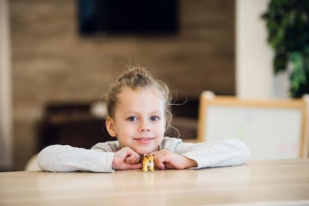 Mooi rustig meisje, zittend aan een houten tafel
