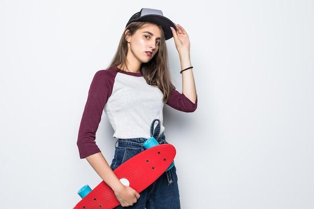 Mooi schaatsermeisje dat rood skateboard in haar handen houdt dat op witte muur wordt geïsoleerd