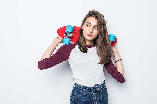 Mooi schaatsermeisje dat rood skateboard op haar rug houdt dat op witte muur wordt geïsoleerd