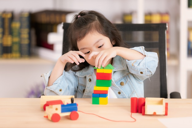 Mooi schattig klein aziatisch meisje in spijkerbroek shirt hout blok speelgoed spelen op het bureau.