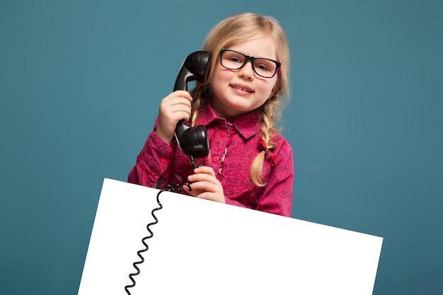 Mooi, schattig klein meisje in roze shirt, zwarte broek en bril houdt lege poster en een telefoongesprek