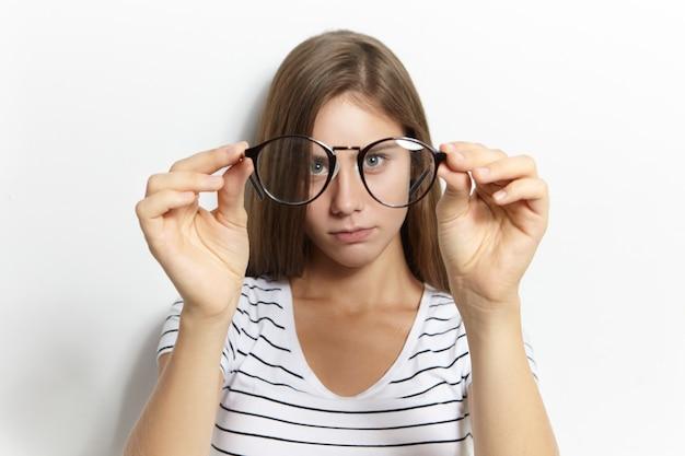 Mooi schattig kortzichtig teeage meisje in stijlvol gestreept t-shirt haar eerste bril opzetten. visiecorrectie, optica, bijziendheid en bijziendheid concept. selectieve aandacht voor brillen