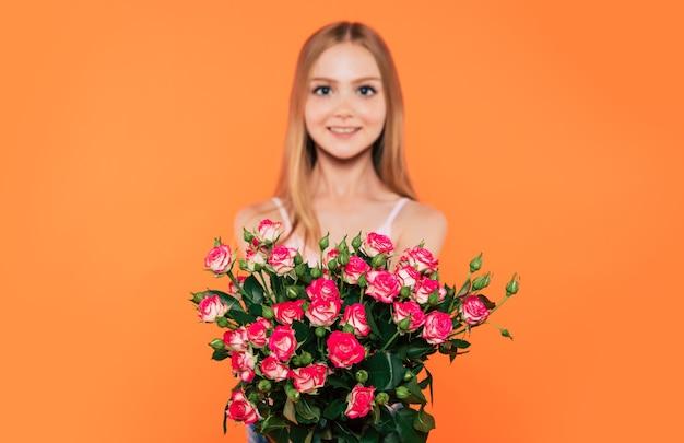 Mooi, schattig, lief, glimlachend blond meisje met gelukkige ogen houdt een groot boeket bloemen geïsoleerd in de studio. verjaardag, feestdagen, valentijnsdag, moederdagconcepten