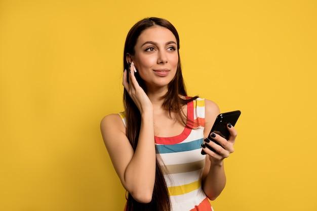Mooi schattig meisje draagt ?? gestripte zomerjurk luisteren muziek in koptelefoon en smartphone gebruikt over gele muur