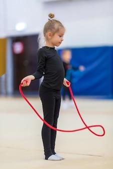 Mooi schattig meisje loopt met een springtouw. gelukkige jonge geitjes glimlachen en springen in de sportschool met spiegels. ze droegen zwarte sportkleding. kinderen leiden een gezonde levensstijl