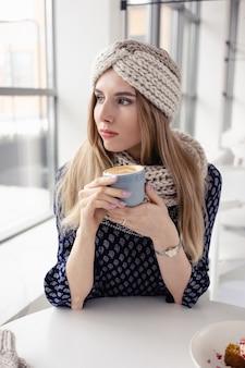 Mooi schattig winter meisje gebreide muts en wanten met koffiemok dragen. aantrekkelijk meisje met warme drank op café achtergrond. koffie drinken en genieten van het leven.