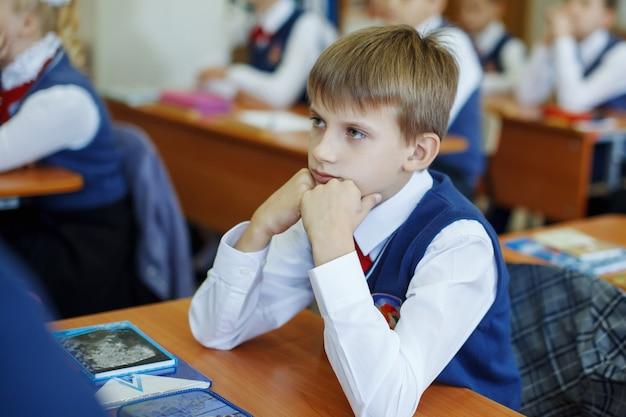 Mooi schoolkind bij een bureau op een vakantie. krijgt onderwijs op de basisschool