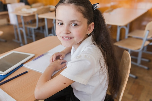 Mooi schoolmeisje dat camera bekijkt