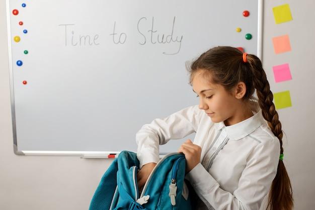 Mooi schoolmeisje dat voor lessen voorbereidt