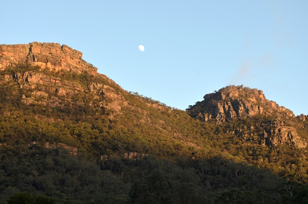Mooi schot van beboste bergen onder een heldere hemel met een zichtbare maan overdag