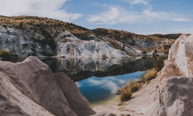 Mooi schot van blue lake in nieuw-zeeland, omringd door rotsachtige heuvels onder een blauwe hemel