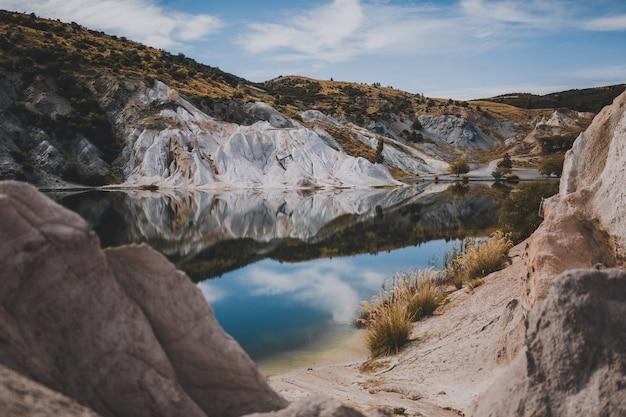 Mooi schot van blue lake, omgeven door heuvels onder een blauwe hemel in nieuw-zeeland
