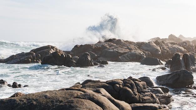 Mooi schot van de golven van de stormachtige oceaan die de stenen op de kust bereikt