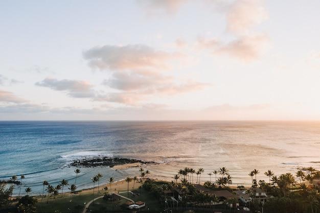 Mooi schot van de kalmerende golven van de oceaan met een landschap van zonsondergang
