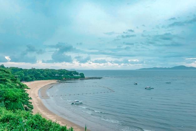 Mooi schot van de kust van een strand met boten op het water onder een blauwe bewolkte hemel
