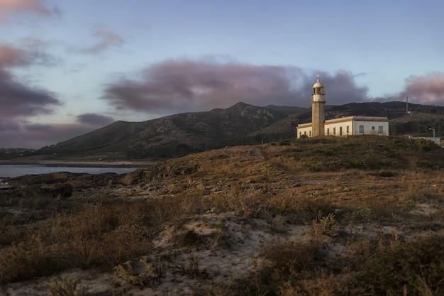 Mooi schot van de larino-vuurtoren op een heuvel in galicië, spanje