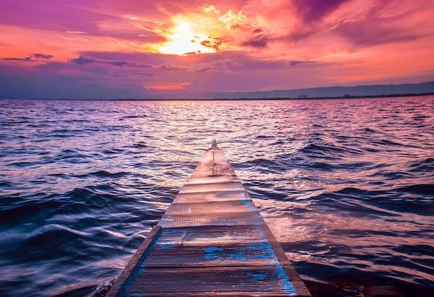 Mooi schot van de neus van een kleine boot die in de zee met verbazingwekkende wolken in de rode hemel vaart