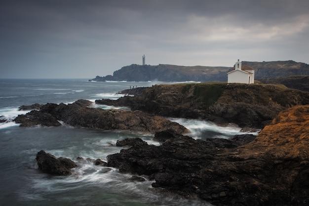 Mooi schot van de oceaan met rotsformaties aan de kust op een bewolkte dag