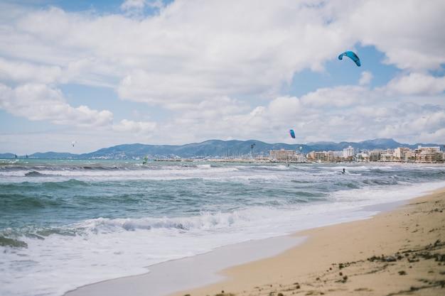 Mooi schot van de oceaangolven en luchtballons op het strand onder de bewolkte hemel