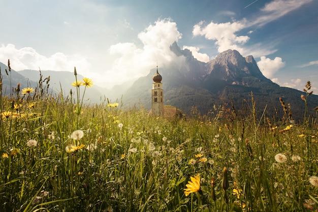 Mooi schot van de st. valentin-kapel, omringd door majestueuze bergen in italië