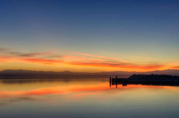 Mooi schot van de weerspiegeling van de oranje zonsonderganghemel in het water