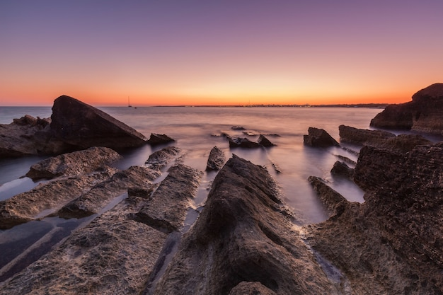 Mooi schot van de zee met kliffen en rotsen tijdens zonsondergang