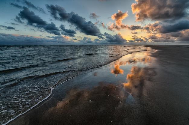 Mooi schot van de zonsondergang die in het overzees nadenkt