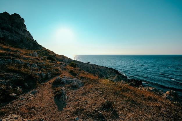 Mooi schot van droge grasheuvel en klip dichtbij het overzees met duidelijke blauwe hemel