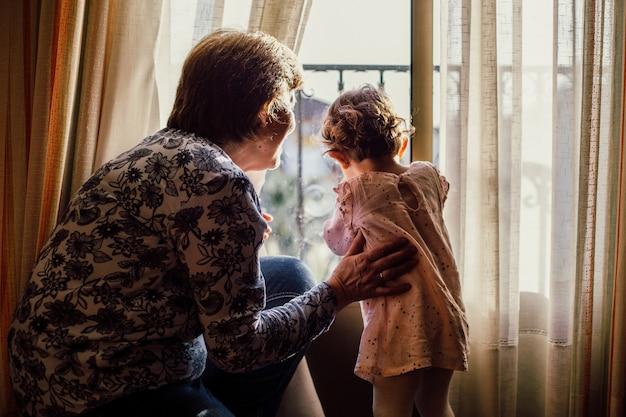 Mooi schot van een bejaarde vrouw en een meisje kijkt door een raam
