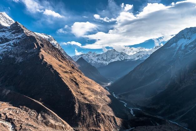 Mooi schot van een bergachtig gebied in de winter en de bewolkte hemel hierboven