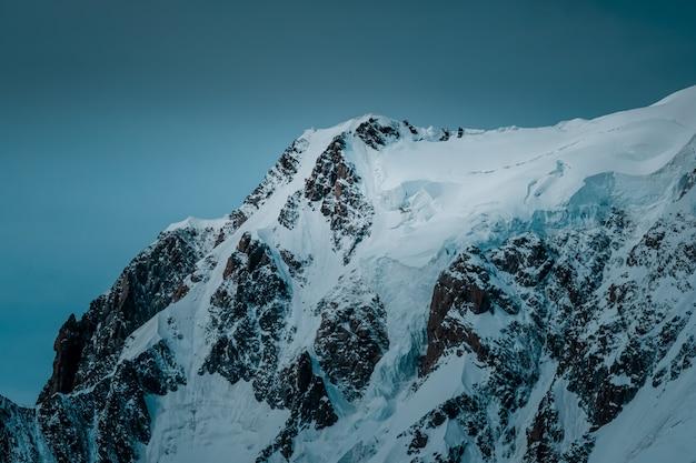 Mooi schot van een besneeuwde berg met een heldere hemel