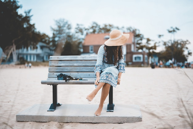Mooi schot van een blootvoetse vrouwelijke zitting op een bank bij het strand met vaag