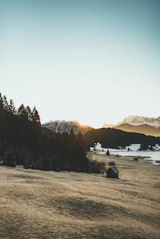 Mooi schot van een heuvel met bomen en een houten hut en bergen op de achtergrond