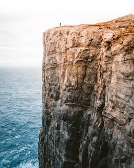 Mooi schot van een hoge rots naast de zee