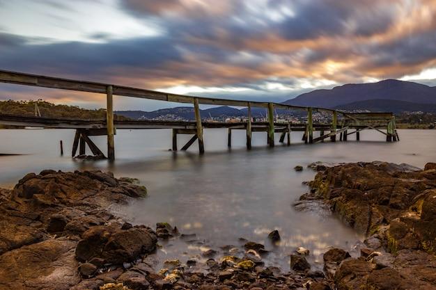 Mooi schot van een lange pier in het water onder de kleurrijke bewolkte hemel