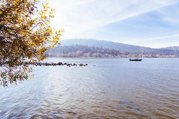 Mooi schot van een meer met een boot die op het met een zonnige hemel vaart