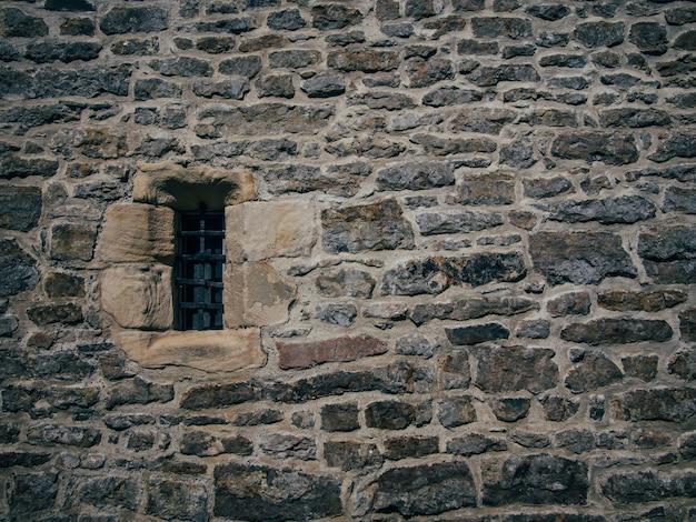 Mooi schot van een oude structuur van steenbaksteen met een geblokkeerd klein venster