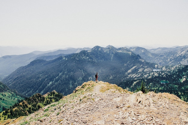 Mooi schot van een persoon die zich op de rand van de klif met beboste bergen