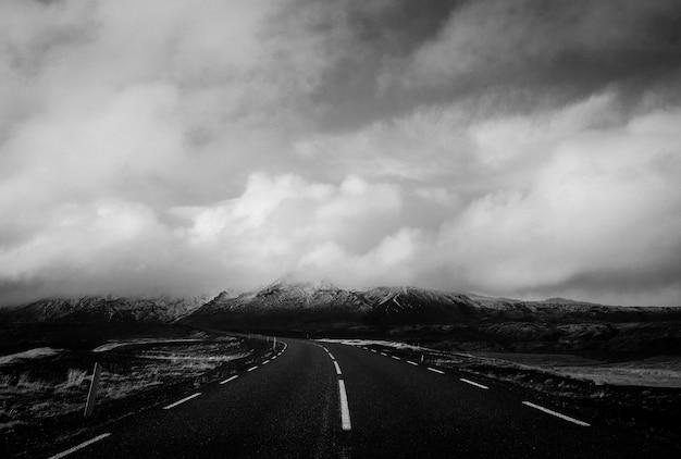 Mooi schot van een smalle weg met adembenemende wolken