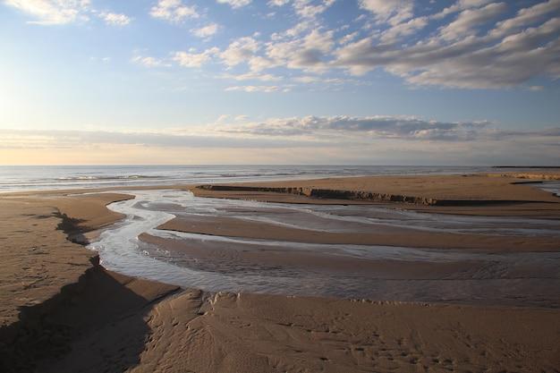Mooi schot van een strandkust onder een blauwe bewolkte hemel